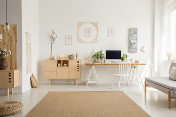 Brown carpet between pouf and grey sofa in white home office interior with chair at desk. Real photo