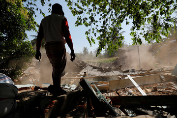 A villager stands near collapsed house at Kayangan district after earthquake hit on Sunday in North Lombok