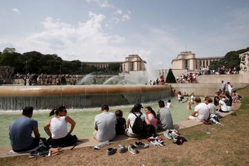 People cool off in the fountains across from the Eiffel Tower as a heatwave with high temperatures continues in Paris