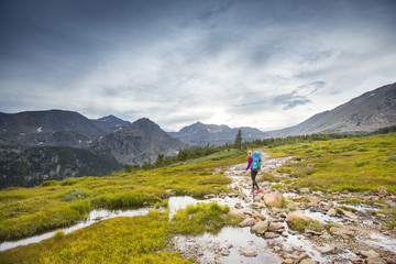 Woman backpacking in the Indian Peaks wilderness on Arapahoe pass trail in Colorado.