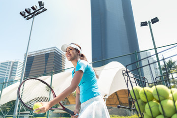 Low-angle view a cheerful beautiful woman ready to serve while playing tennis in a developed city with modern facilities
