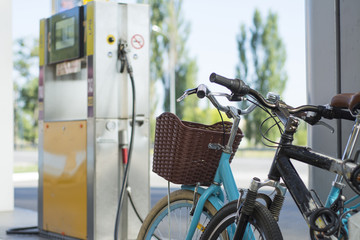 Two bicycles on the background of an automobile gas station.