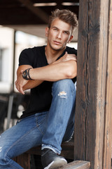 natural handsome young male model with a hairdo in a black T-shirt and jeans sits on a wooden veranda