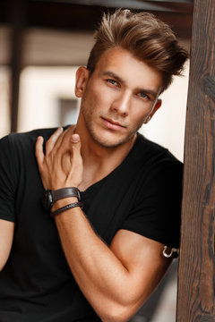 Fresh portrait of a beautiful young model man in a black T-shirt on a street near a wooden pillar