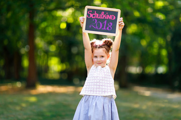 """Happy little kid girl holding empty chalk desk in hands. Schoolkid on first day of elementary class. Healthy adorable child outdoors, in green park. On desk """"Schoolchild 2018"""" in German"""