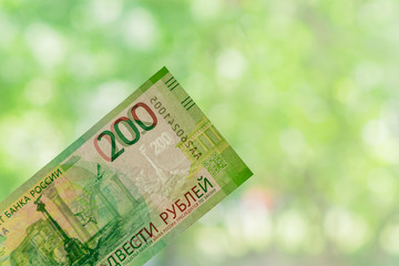 new russian banknote against green bokeh background. two hundred roubles. Cash paper money.