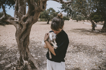 Woman holding goat in olive grove