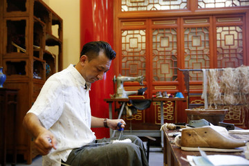 "Cobbler Cai Wenke works on a ""thousand-layer""  cloth shoe at the demonstration workshop of the Neiliansheng shoemaker in Beijing"