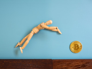 Wooden puppet jumping from the wooden floor in the air to catch the bitcoin.