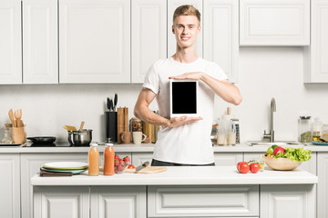 handsome young man holding tablet with blank screen in kitchen