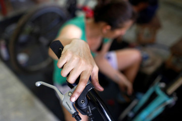 A member of Velo Cuba, a bicycle workshop and rental, tests the gear shifters of a bicycle in Havana