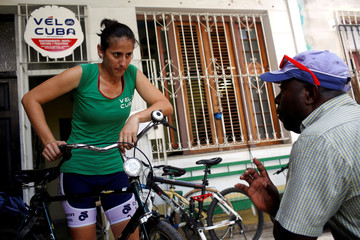 A member of Velo Cuba, a bycicle workshop and rental, listens to a customer outside the workshop in Havana