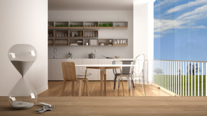 Wooden table, desk or shelf with crystal modern hourglass measuring the passing time in a countdown over blurred minimalistic kitchen, architecture interior design, copy space background