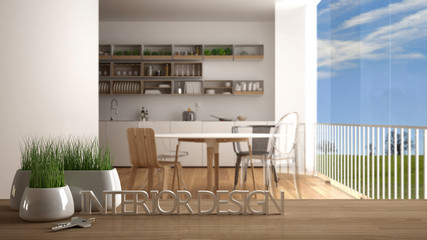 Wooden table, desk or shelf with potted grass plant, house keys and 3D letters making the words interior design, over blurred modern kitchen, project concept copy space background