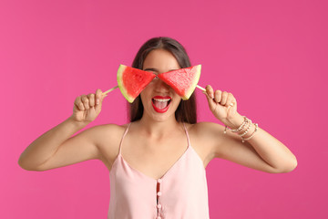 Beautiful young woman posing with watermelon on color background
