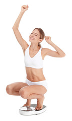 Happy young woman satisfied with her diet results using bathroom scales on white background