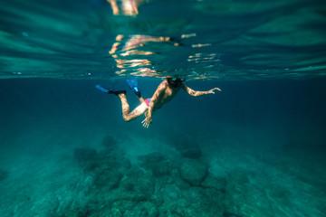 Anonymous boy snorkeling in sea