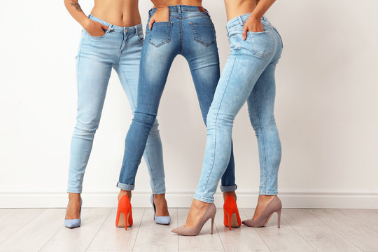 Group of young women in jeans near light wall