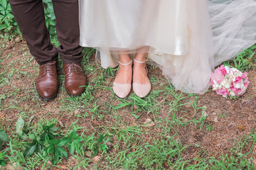 Cute cropped picture of groom's and bride's shoes standing together on the grass