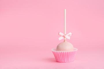 single festive icing cake pop over pink background, close up