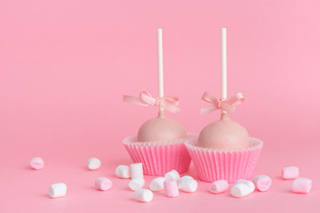 couple festive icing cake pops and marshmallows over pink background, concept of Valentines day