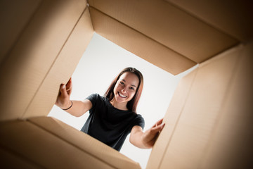 The surprised woman unpacking, opening carton box and looking inside. The package, delivery, surprise, gift, lifestyle concept. Human emotions and facial expressions concepts