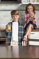 little brother and sister with glasses of orange juice at kitchen