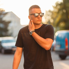 Hipster man with a hairdo in stylish sunglasses and a black fashion T-shirt at sunset