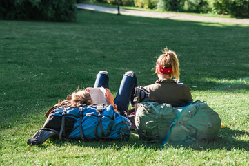 Relaxing summer day in a Danish park, young women travellers lounging on the grass. Concept of hygge.