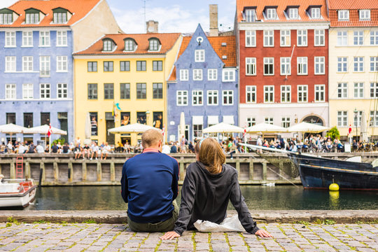 Tourists enjoying the scenic summer view of Nyhavn pier. Colorful building facades with boats and yachts in the Old Town of Copenhagen, Denmark