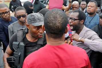 A man reacts next to a member of security forces at the entrance of the National Assembly in Abuja