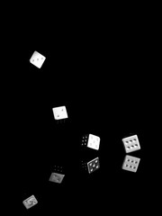 Tumbling shiny dice, on black background. Business concept, success etc.