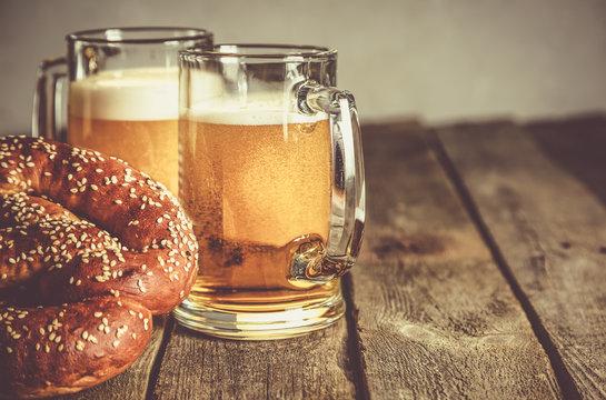 Oktoberfest concept - pretzels and beer on rustic wood background
