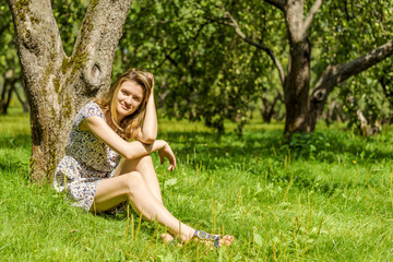 Young cute woman sits and rests in the garden under a tree