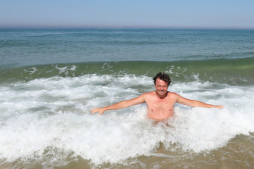 man bathes on the beach as ocean waves crash behind him