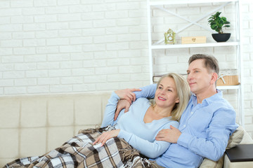 Couple at home on the couch talking and smiling