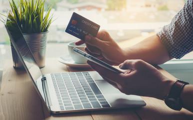 Obraz Man holding credit card payment shopping online on smart phone - fototapety do salonu