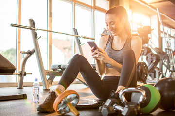 Cheerful sporty girl using phone while sitting on mat in gym