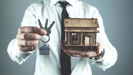 Real estate agent holding wooden house and keys. Real estate concept