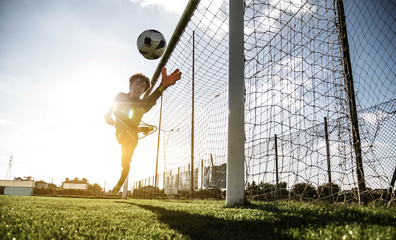 Goalkeeper jumping at stadium over sunsetlight