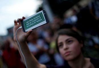 A journalist films with her mobile during a protest on the 10th anniversary of Georgian Russian war in front of the building of Russian Federation Interests Section of the Embassy of Switzerland in Tbilisi