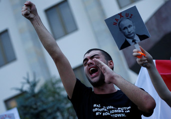 A man attends a protest on the 10th anniversary of Georgian Russian war in front of the building of Russian Federation Interests Section of the Embassy of Switzerland in Tbilisi