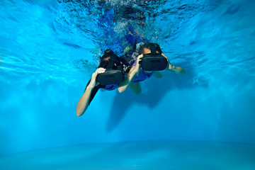 A little girl with her mother swim and play under water in the pool in virtual reality glasses on her head. Shooting underwater. The horizontal orientation of the image