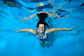 A beautiful young girl in a dress floating underwater in the pool on a blue background with her hands out to the side, looking at the camera and smiling. Portrait. Shooting underwater