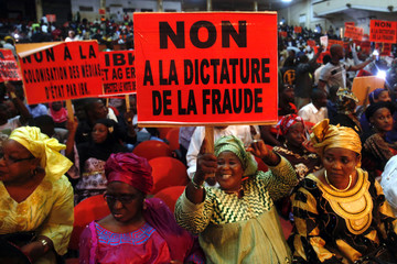 Opposition supporters hold up placards during a protest against what they say were vote irregularities, in Bamako