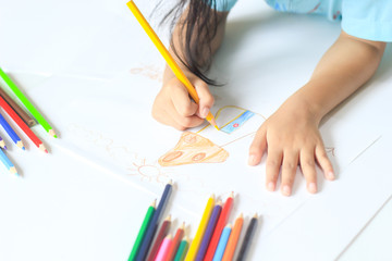 A girl drawing with color pencil on white paper.