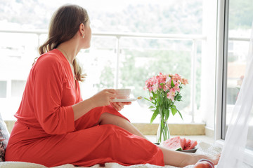 Young Blonde woman in a red robe  drinks coffee against wide window background and having lazy morning