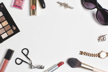 flat lay of cosmetics, eyeshadow palettes, makeup brushes and lipsticks with women's fashion accessories on white background.