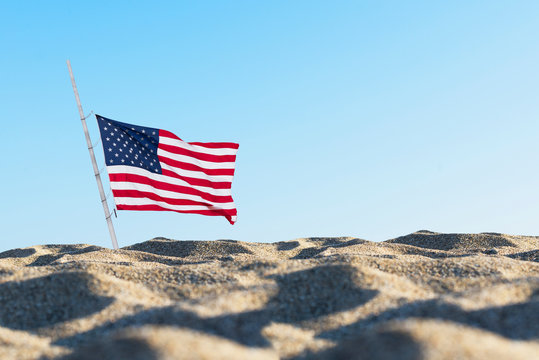 American flag in the sand against a blue sky. . Concept