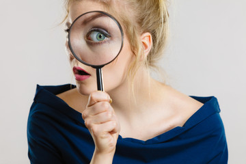 Woman holding magnifying glass investigating